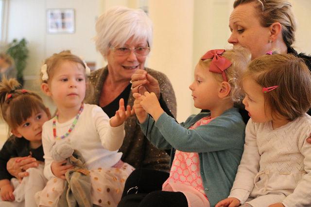 Flere små søde piger som sidder med Soffie Dalsgaard og snakker.